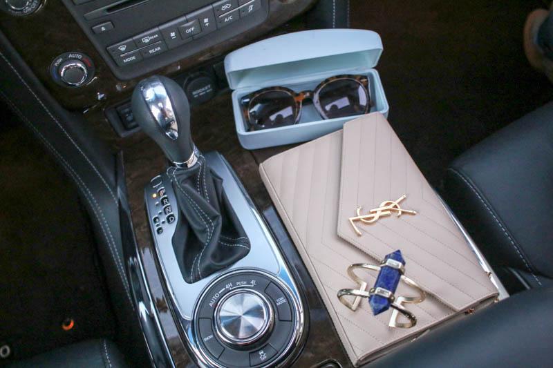 Hertz console with YSL bag, kendra scott cuff and karen walker sunglasses